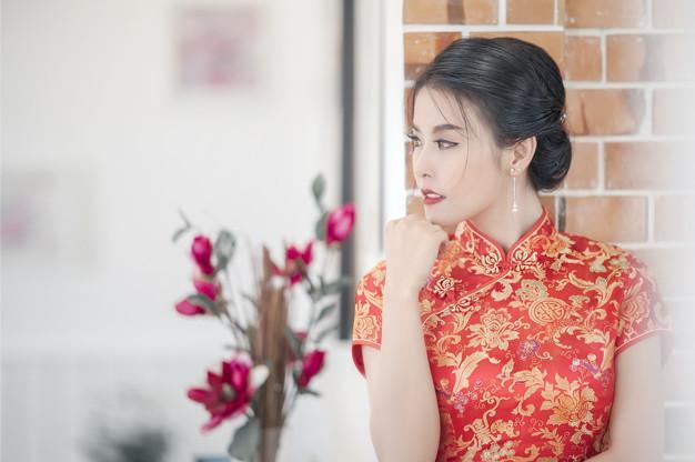 An Asian woman in a traditional cheongsam